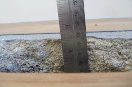 Amitico flooring heating repair hole in concrete measured with ruler